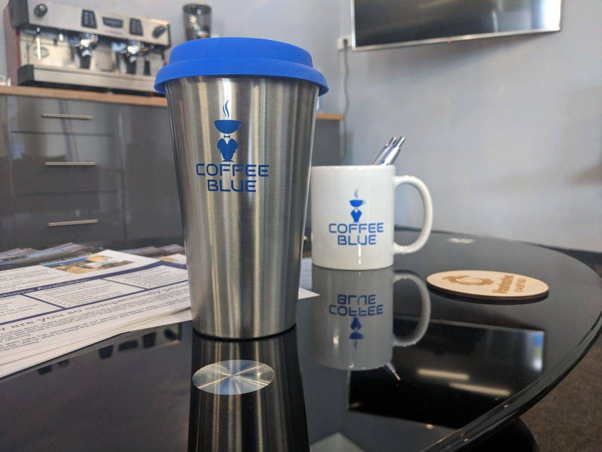 Reusable coffee cup and mug on a coffee table