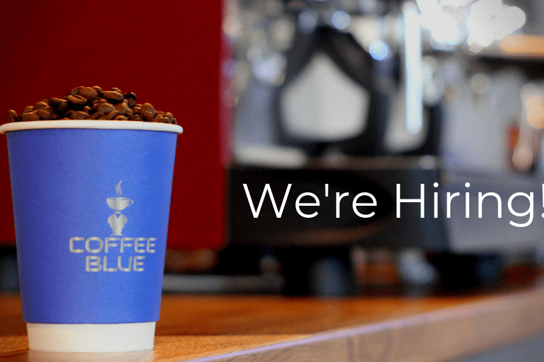 """Coffee Cup in foreground. Text overlay that says: """"We're Hiring!"""""""